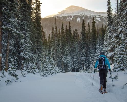 a backcountry skier hikes toward a mountain view