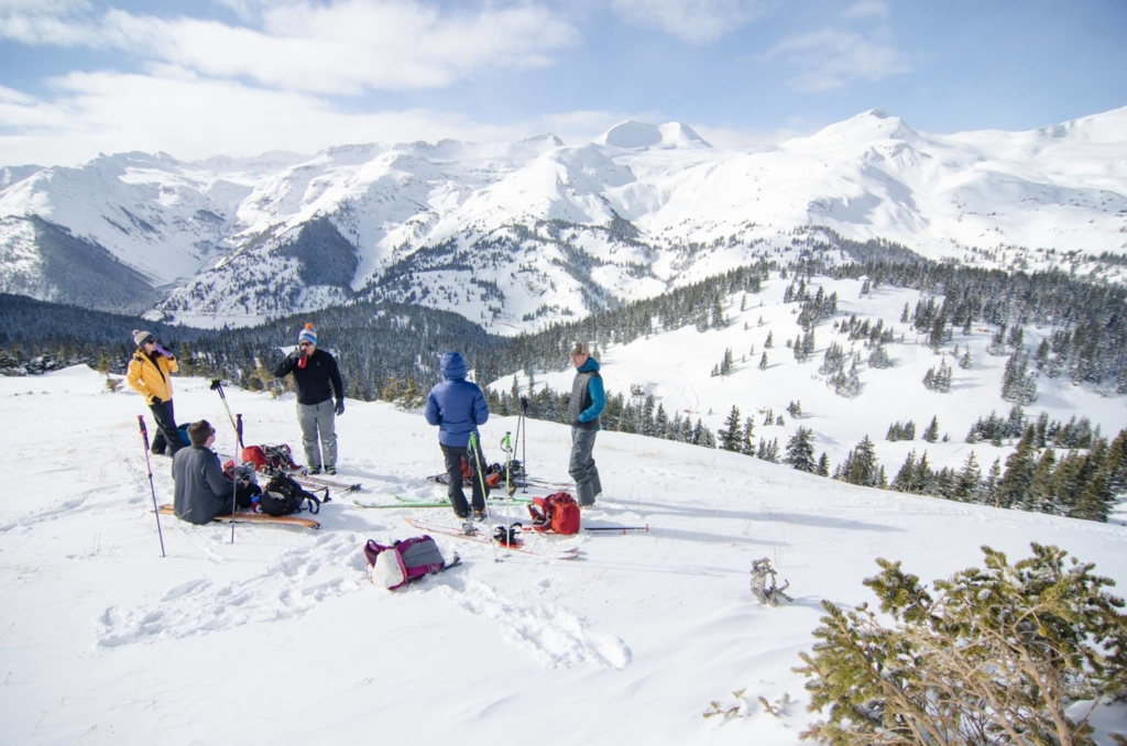 A group of backcountry skiers and splitboarders take in a snowy mountain view.