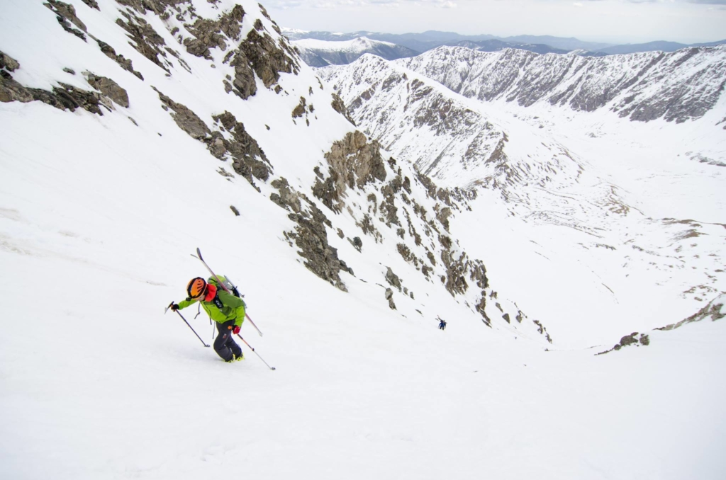 A backcountry skier hikes up a remote snow chute in the Rocky Mountains.