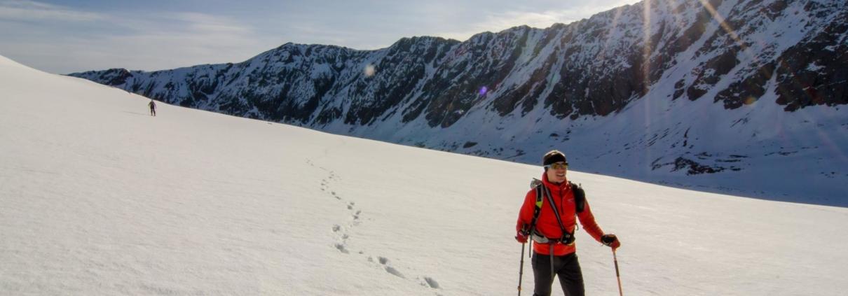 a backcountry skier explores the mountains on touring skis
