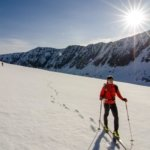 a backcountry skier explores the mountains on touring skis