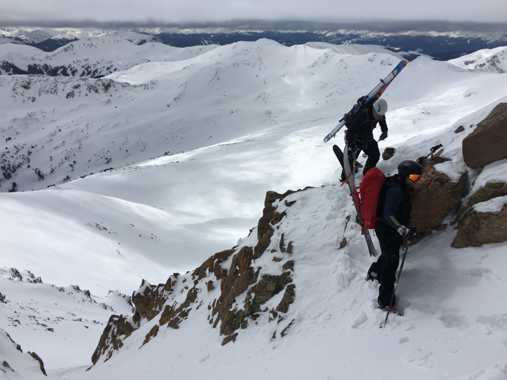Two backcountry skiers climb to the top of a remote mountain ridge.