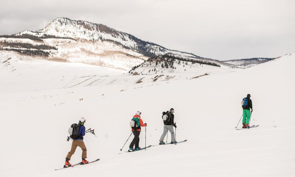 Four backcountry skiers explore the mountain terrain of Bluebird Backcountry.