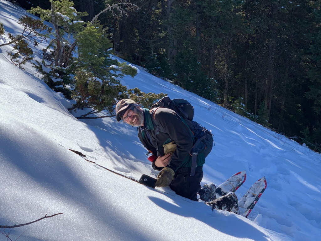a ski patroller evaluates a snow slope for avalanche safety