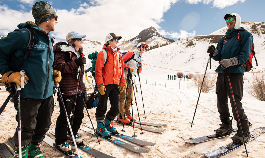 a group of backcountry skiers gathers on the mountain for a backcountry ski clinic