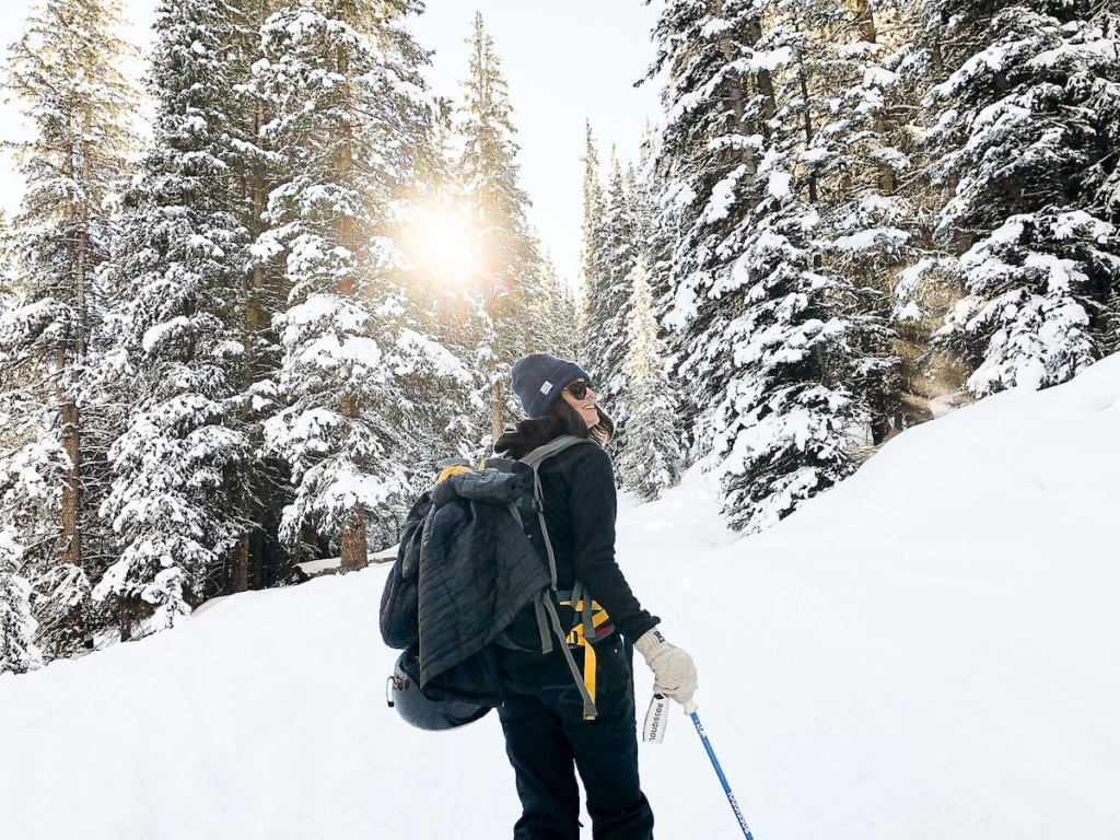 a backcountry skier on dawn patrol looks at sunrise through snowy trees