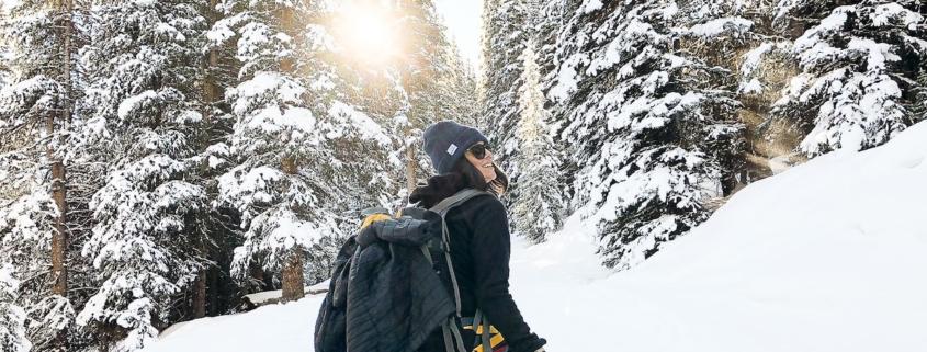 a backcountry skier on dawn patrol looks at sunrise through snowy trees