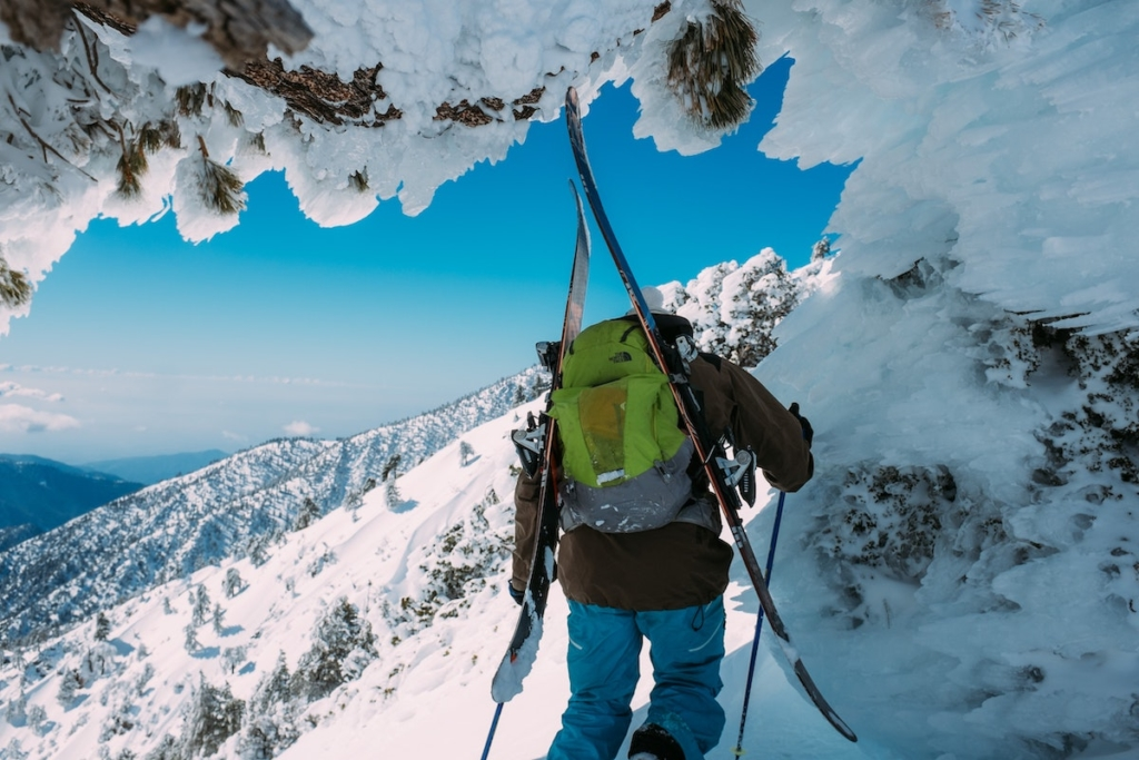 a backcountry skier with skis on her back hikes under a rocky ridge