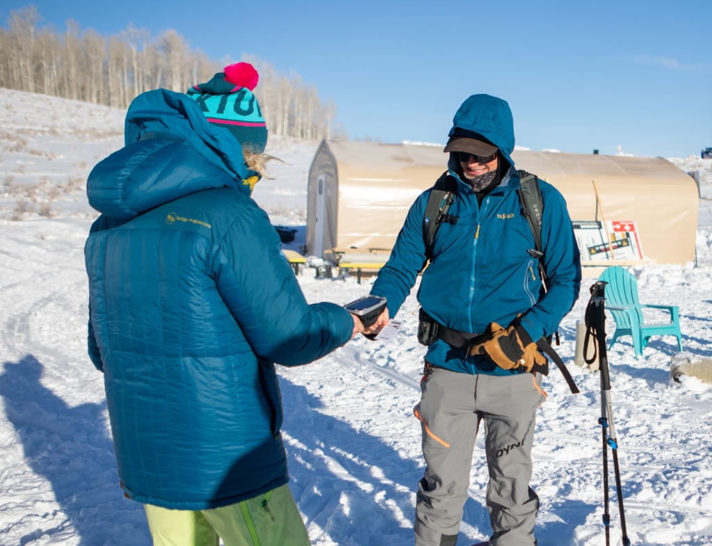 Two backcountry skiers with Big Agnes jackets perform a beacon check
