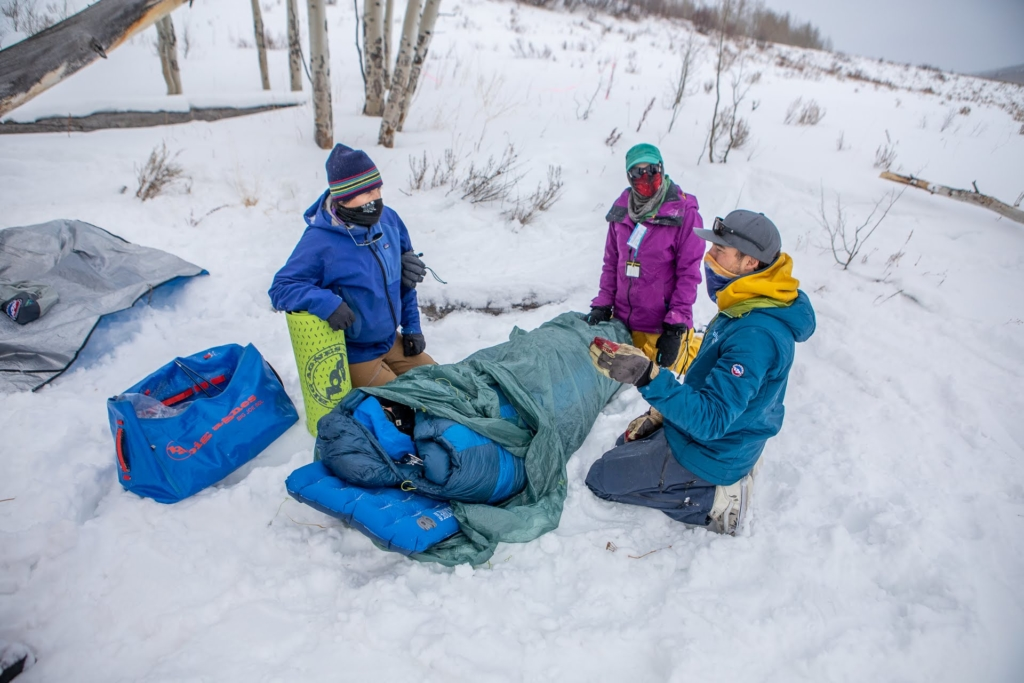 Three backcountry skiers gather around a person in a sleeping bag and discuss layering for backcountry skiing