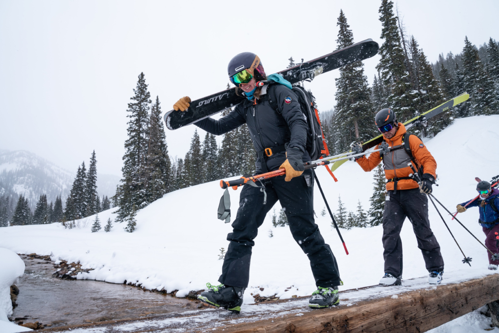 Two backcountry skiers carry their skis across a bridge in the snow