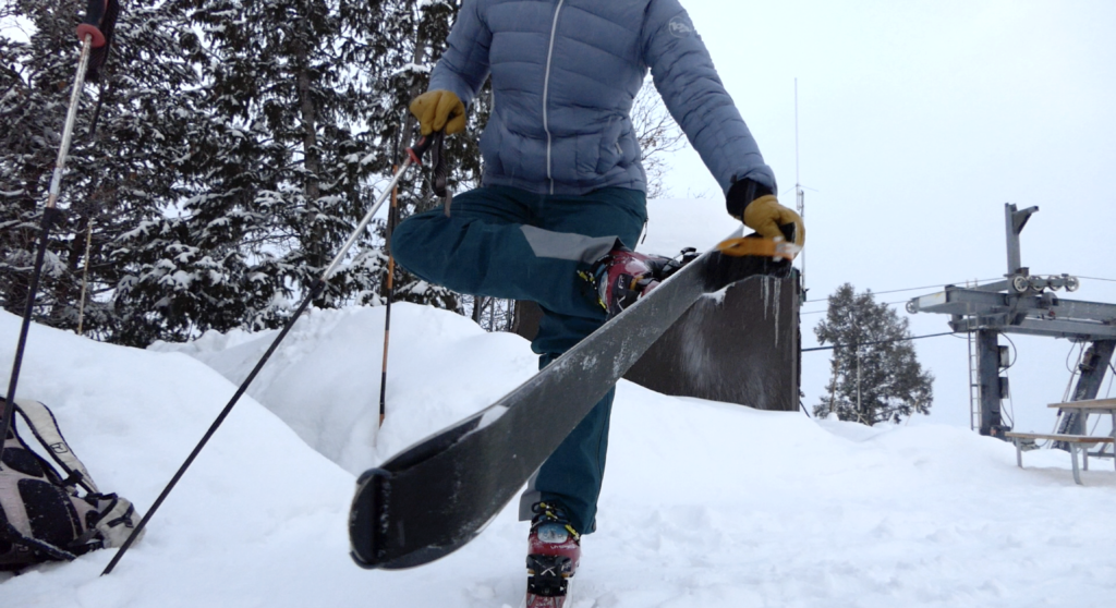 A backcountry skier wears an insulated jacket while ripping skins