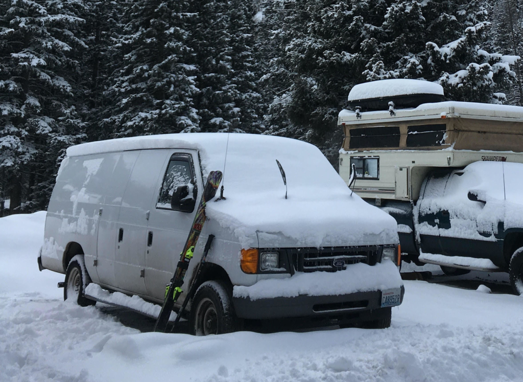 Skis lean against a ford van used for winter camping