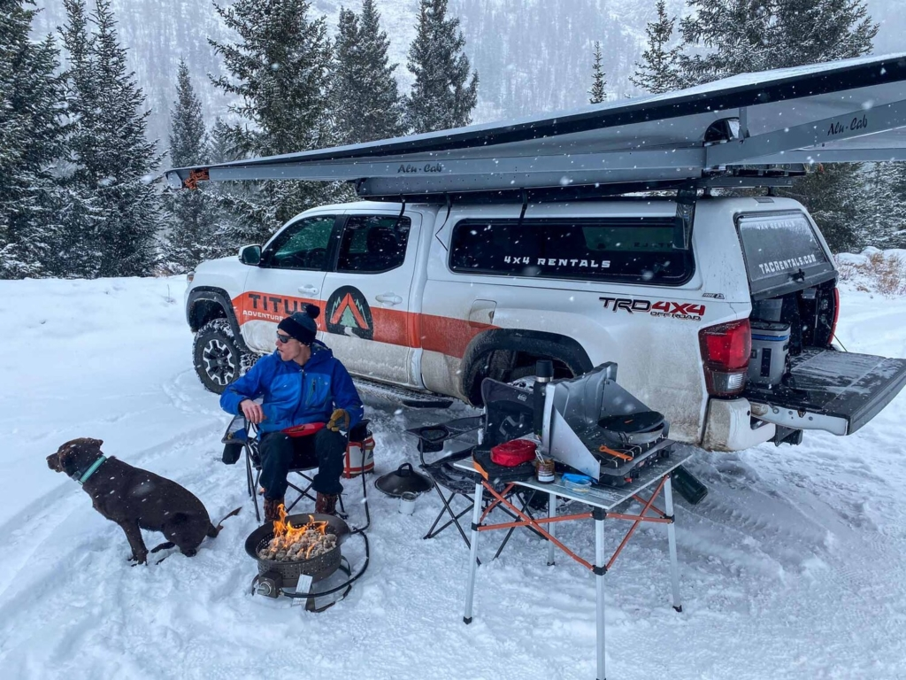 a truck setup for winter camping with a portable fire pit outside