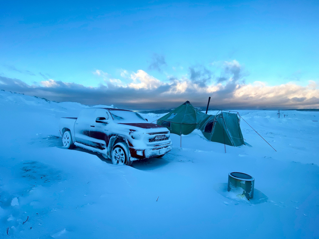 A winter tent beside a snowy truck at sunrise