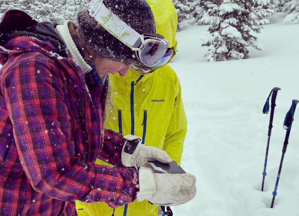 Two backcountry skiers look at snow crystals during an avalanche safety course.
