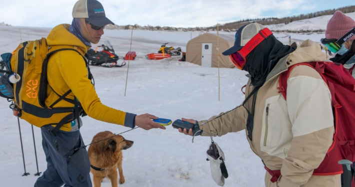 A skier in a yellow jacket reaches out to perform a beacon check with a backcountry skier in a brown jacket