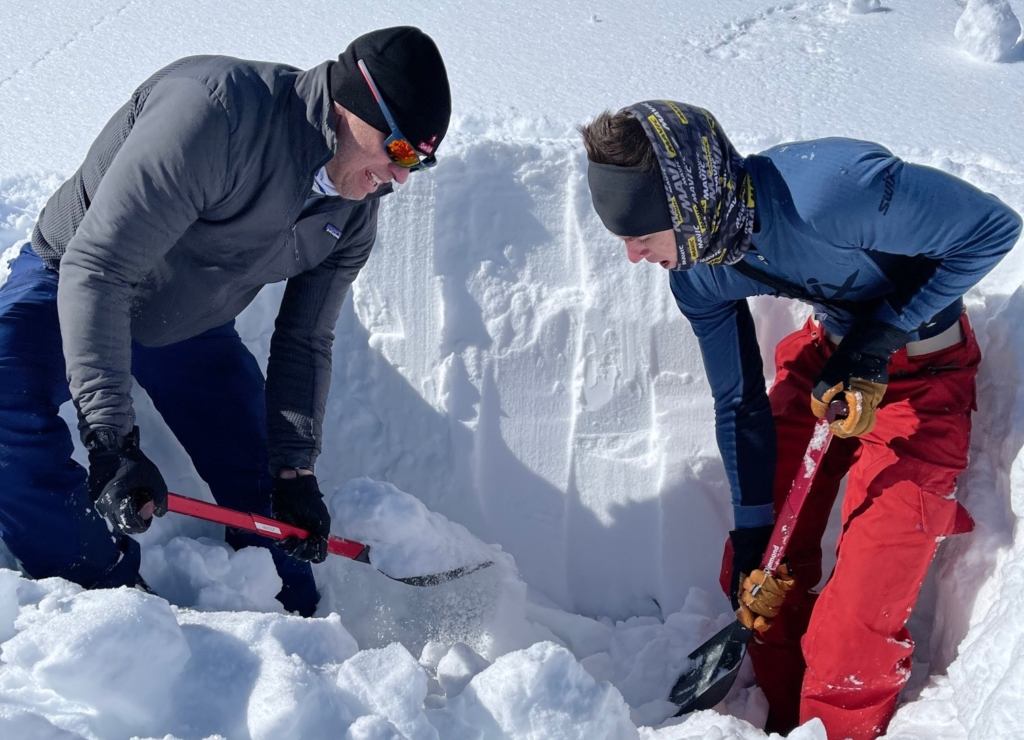 Two backcountry skiers with avalanche shovels practice avalanche rescue digging techniques