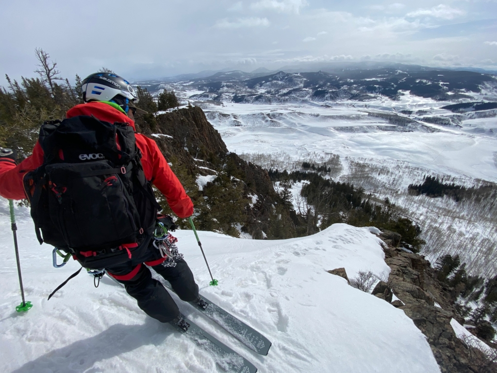 skier looks over the edge of a rocky couloir