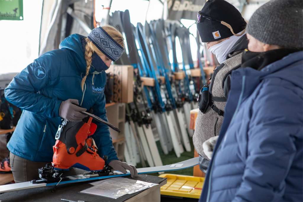 A ski tech in a blue jacket tunes a pair of skis